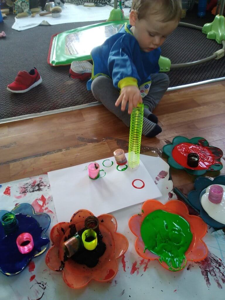 slinky, mark making, painting, fun, apron, active learning, exploring, learning, planned, paint, patterns, experiences